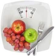 Äpfel, Trauben, eine Gabel und ein Messer auf Waage