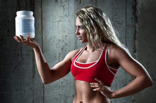 Sportliche Frau, die einen Behälter mit Protein hält