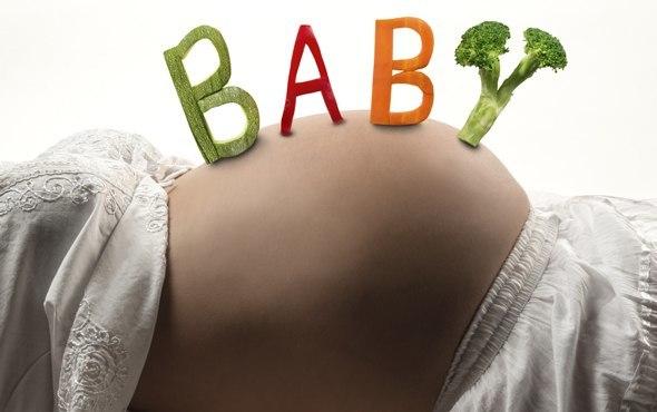 Baby buchstabiert mit Gemüse auf schwangerem Bauch