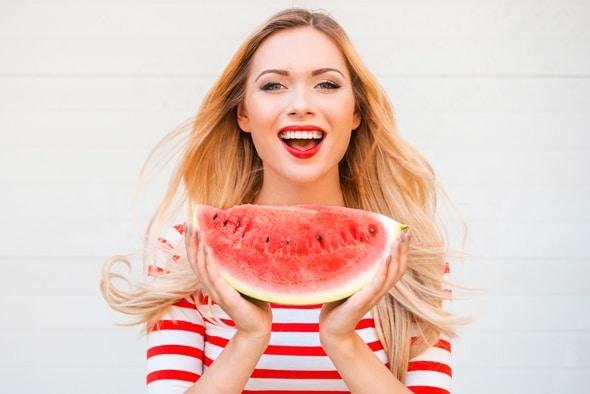 Blondine hält eine große Scheibe Wassermelone