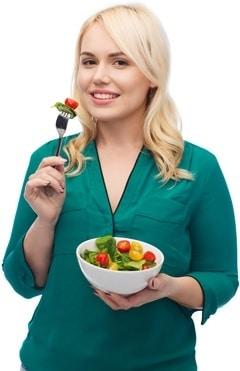 Blondine im grünen Hemd, das Salat isst