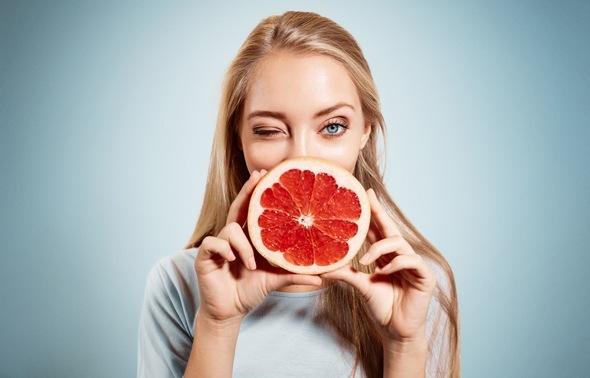 Blond mit Grapefruit, zwinkert