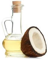 Flasche Kokosöl und eine halbe Kokosnuss