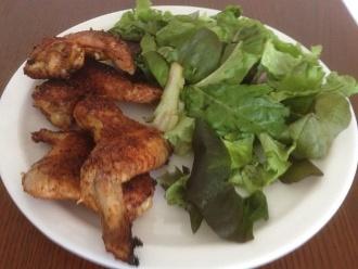 Gebratene Hühnerflügel mit Salat auf der Seite