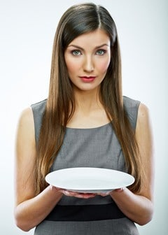 Brünette Geschäftsfrau mit leerem Teller
