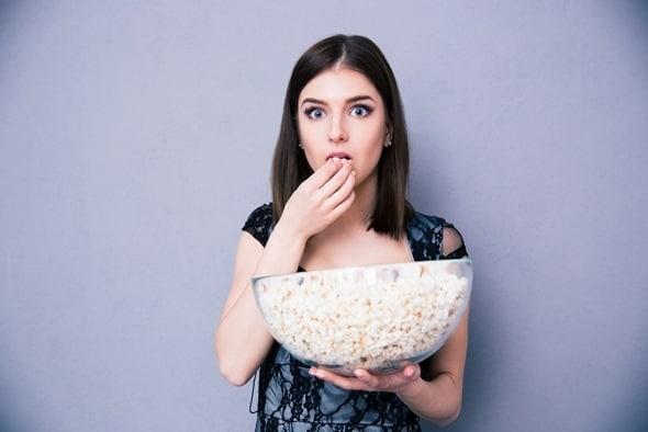 Brünette, die Popcorn aus einer großen Schüssel isst