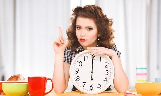 Brünette hält eine Uhr und wartet darauf zu essen