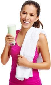 Brünette hält einen Protein-Shake und lächelt