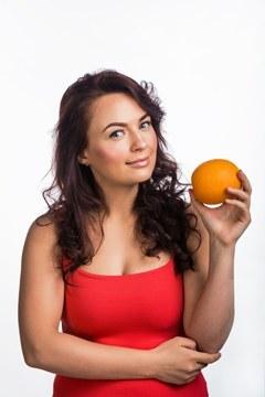 Brünette hält eine Orange