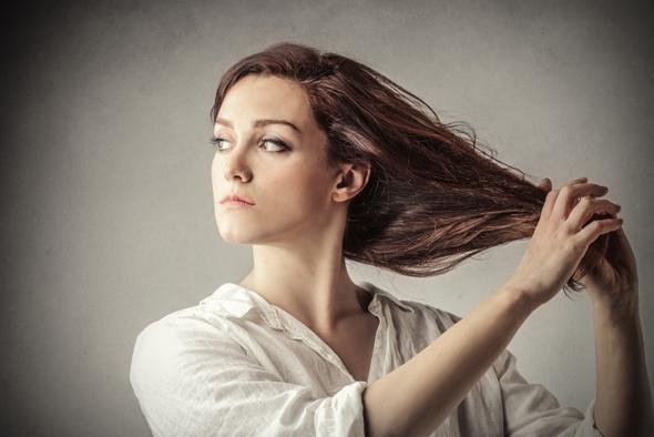 Brünette hält ihr langes Haar in ihren Händen