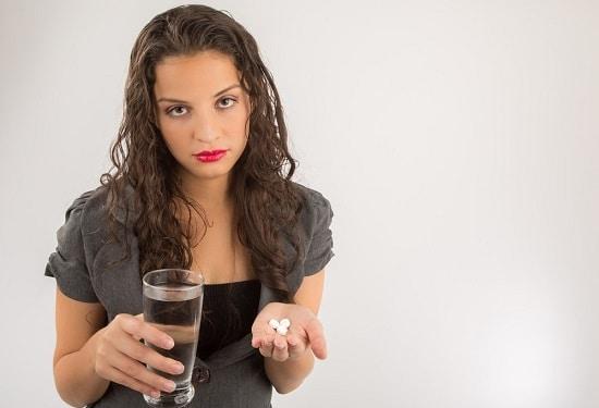 Brünette hält Pillen und Wasser