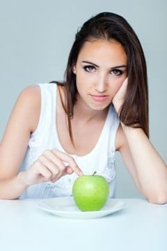 Brünette mit Apfel auf Teller