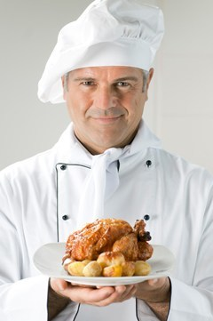 Chef Holding Teller mit Huhn und Kartoffeln