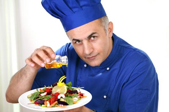 Chefkoch, der Olivenöl auf einen Salat gießt