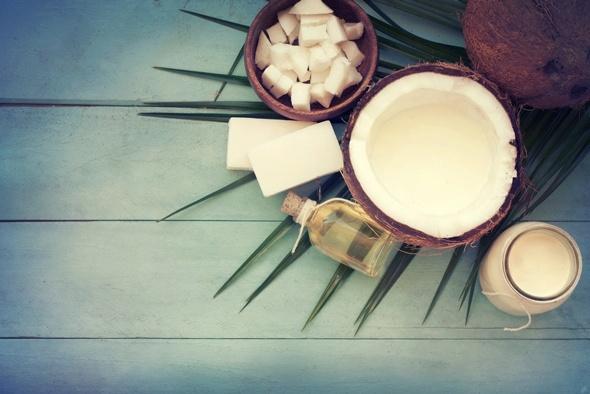 Eine Kokosnuss und Kokosnussöl mit einem blauen Hintergrund