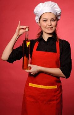 Köchin, die eine Flasche Olivenöl hält