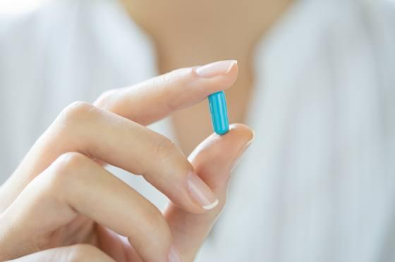 Weibliche Hand, die eine blaue Kapsel hält
