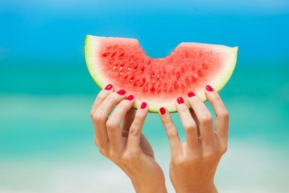Weibliche Hände, die eine Wassermelone halten