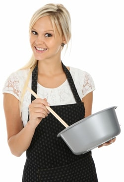 Frau in der Schürze mit Kochschüssel und Löffel