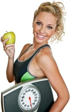 Fit Frau hält eine Waage und einen Apfel