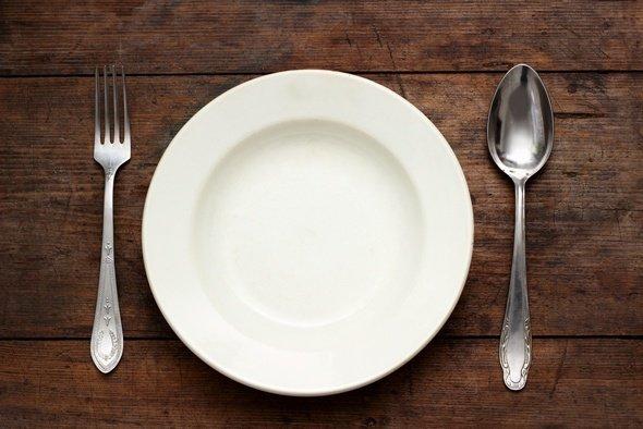 Gabel, Löffel und eine leere Platte auf einem Holztisch