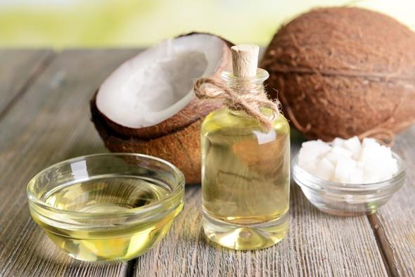 Fraktioniertes Kokosöl in einem Glas und einer Schüssel