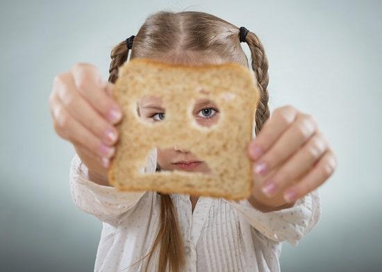 Mädchen, das durch eine Scheibe Brot schaut