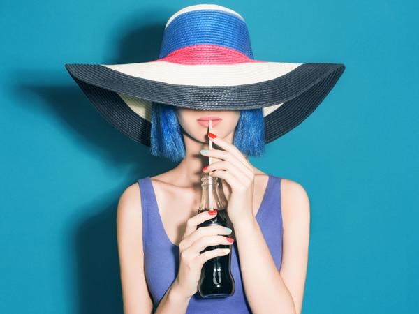 Mädchen mit einem Hut und einer blauen Perücke, die Soda trinkt