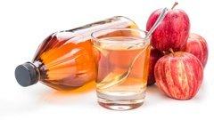 Ein Glas und eine Flasche Apfelessig und einige Äpfel