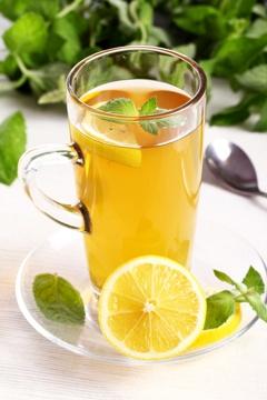 Glasbecher mit Tee und Zitronen