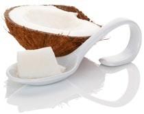 Eine halbe Kokosnuss und ein Löffel mit Kokosöl