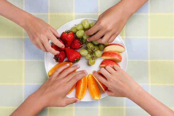 Hände, die Fruchtstücke eines Tellers nehmen