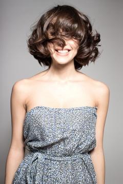 Glückliche Brünette mit den Haaren, die ihre Augen bedecken