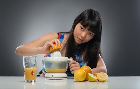 Intensive Frau, die frische Orangen entsaftet