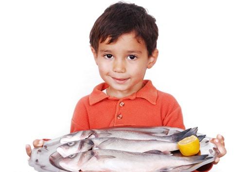 Kleiner Junge hält Fisch
