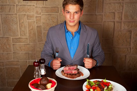 Mann im Restaurant, das Steak isst