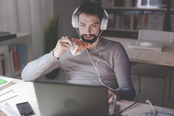 Mann, der Pizza vor seinem Laptop isst