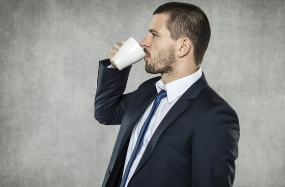 Mann im Anzug, der Kaffee trinkt