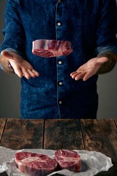 Mann, der ein Stück Fleisch in die Luft wirft