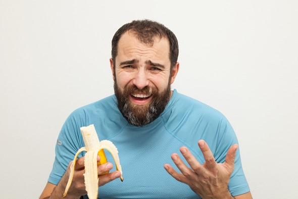 Mann unglücklich über das Essen einer Banane