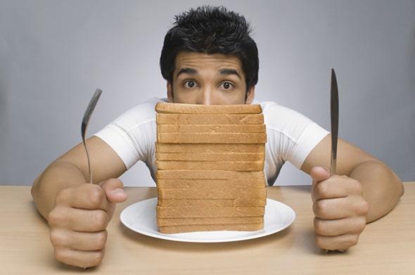 Mann mit einem Stapel Brotscheiben
