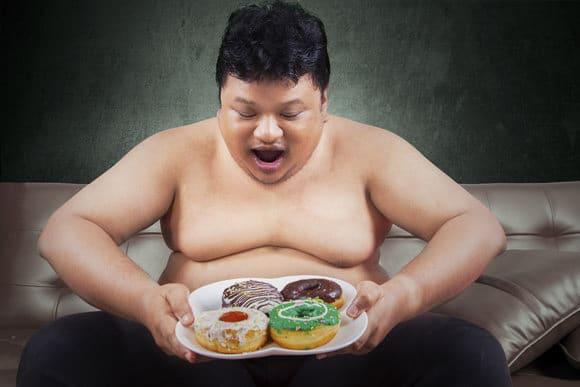 Übergewichtiger Mann, der Donuts betrachtet