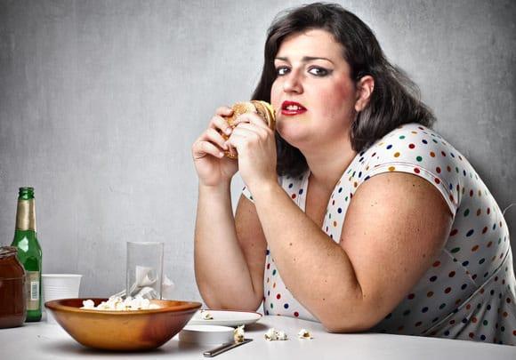 Übergewichtige Frau, die Junk Food isst