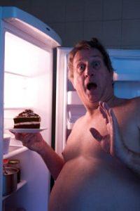 Übergewichtiger Mann, der Kuchen isst