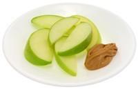 Teller mit Erdnussbutter und Apfelscheiben