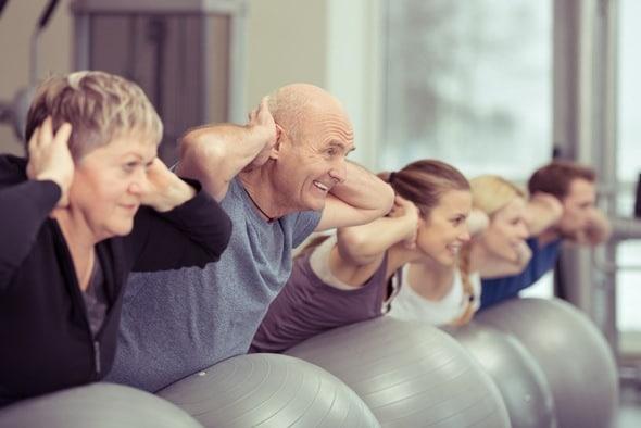 Älterer Mann in einer Fitnessklasse mit jüngeren Leuten