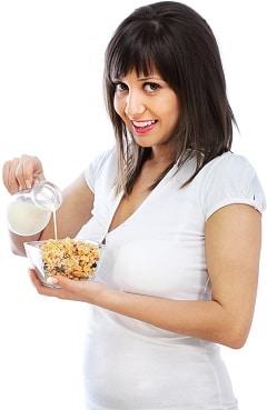 Lächelnde Brünette, die Milch auf Müsli gießt
