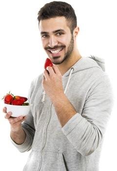 Lächelnder Mann, der Erdbeeren isst