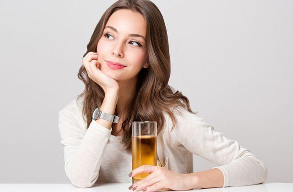 Denkende Frau, die Glas Apfelsaft hält
