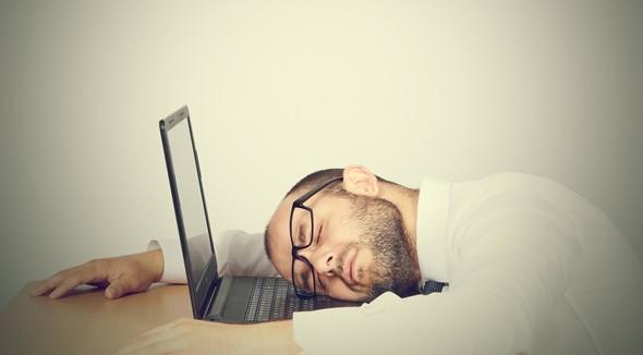 Müder Mann, der mit seinem Kopf auf seinem Laptop schläft
